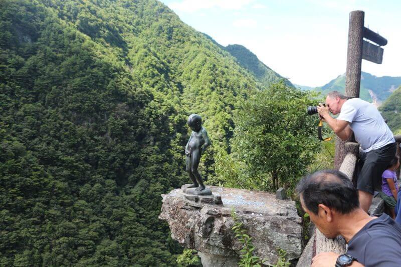 祖谷渓の小便小僧と、それを撮影する外国人観光客
